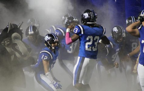 Wolves' linebacker Jared Brumfield (#23) leads Plano West out of the tunnel against McKinney on Friday.