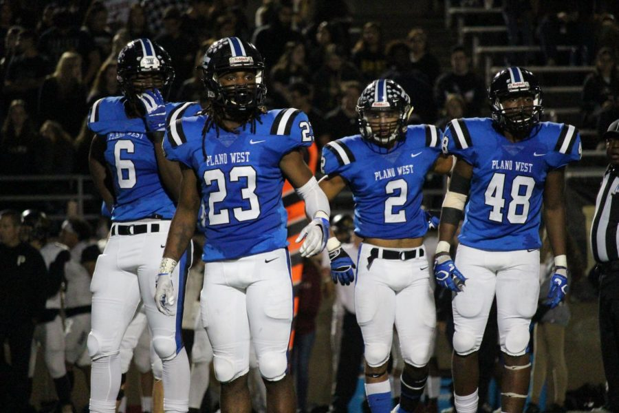 Wolves' defensemen Shemar Pearl (#6), Jared Brumfield (#23), Jacob Stephens (#2), and Tabron Yates (#48) look to the sideline for a playcall.