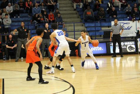 Wolves' point guard Daylen Minor (#1) dribbles the ball around a screen set by Alec Zambie (#20).